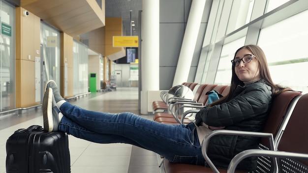 退屈な若い女性がホールに座って空港で彼女の飛行を待っています
