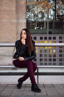 バス停で待っている退屈な若い女性