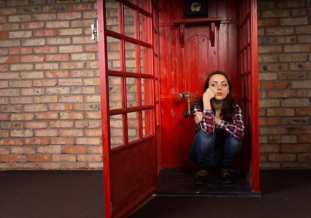 不機嫌そうな表情で床に座っている公衆電話ブースで電話を待っている退屈な若い女性