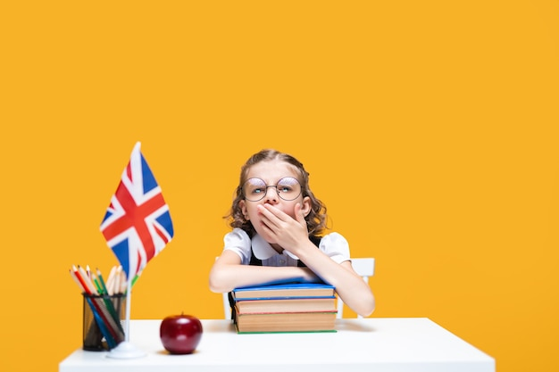 Boring caucasian schoolgirl sits at the desk with stack of books english lesson great britain flag