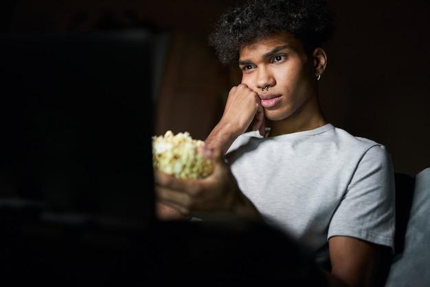 映画を見ながら、ソファに座ってポップコーンボウルを持って退屈そうに見える退屈な映画の若い男