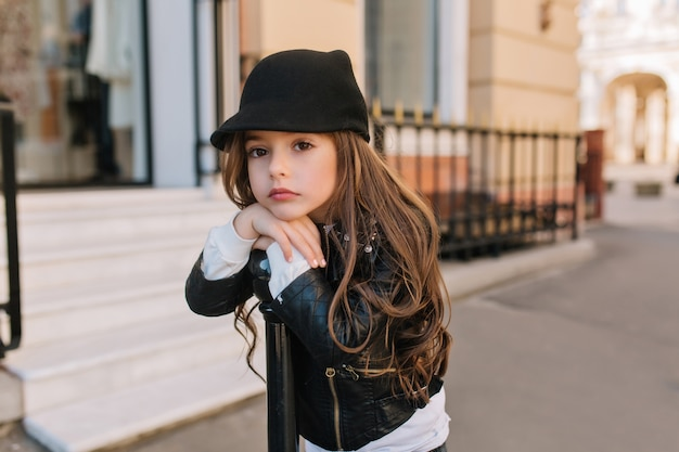 Boring lovely little girl in cute black hat waiting for mother outside in front of beauty saloon.