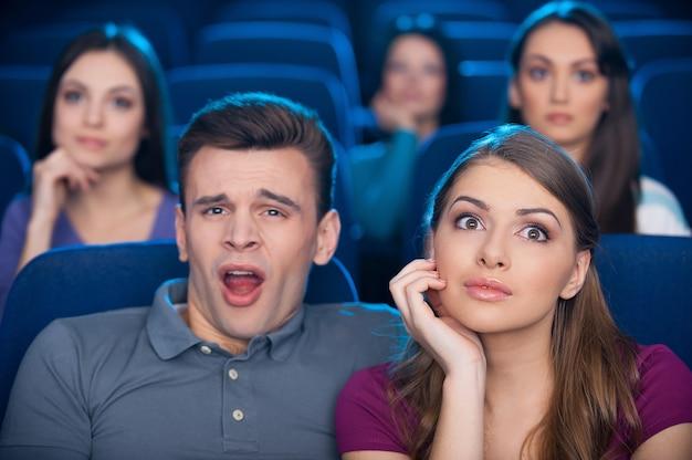 Скучный фильм? скучно молодой человек сидит рядом со своей возбужденной женщиной во время просмотра фильма в кинотеатре