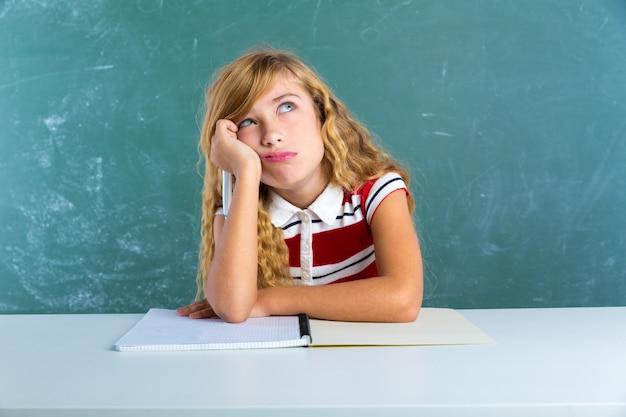 Boring sad expression student schoolgirl on desk