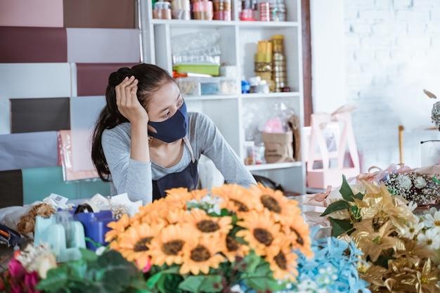エプロンとフェイスマスクを身に着けている退屈な女性の花屋は、朝の日に顧客を待っているテーブルバケツの花に寄りかかって