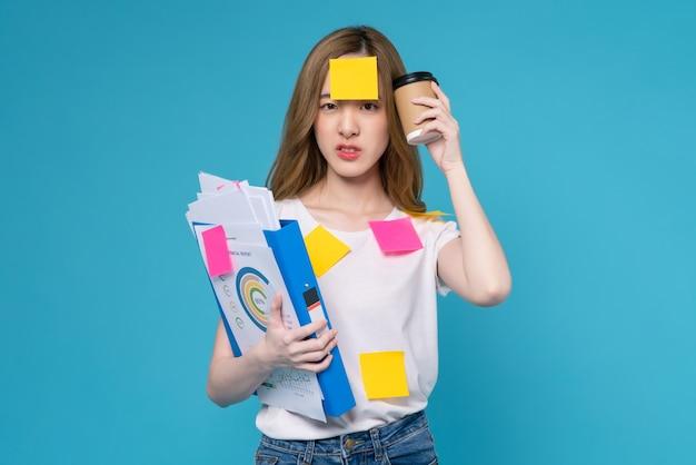 커피 컵과 얼굴에 스티커 메모가 있는 문서 파일을 들고 있는 지루한 젊은 아시아 여성은 스튜디오 촬영 파란색 배경에 서 있습니다.