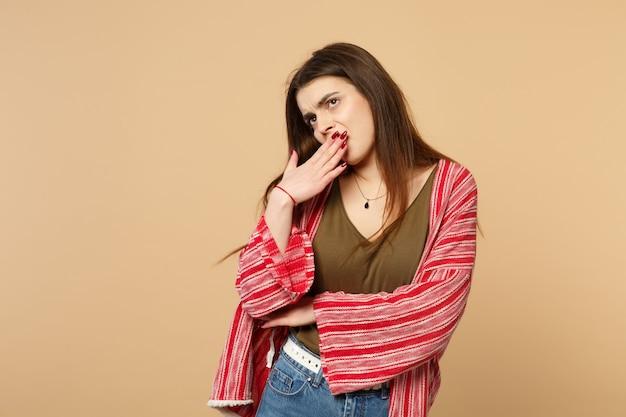 スタジオでパステルベージュの壁の背景に分離された手で見上げる、あくび、手で口を覆うカジュアルな服装で退屈な若い女性。人々の誠実な感情、ライフスタイルのコンセプト。コピースペースをモックアップします。