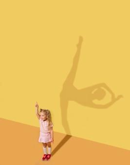 감정을 일으키기 위해 태어났습니다. 어린 시절과 꿈의 개념. 자녀와 함께 개념적 이미지입니다. 스튜디오 벽에 그림자가 그려져 있습니다. 어린 소녀는 발레리나, 발레 댄서, 연극 예술가가되기를 원합니다.