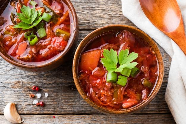 Borsch, beet soup in a wooden bowl with fresh herbs