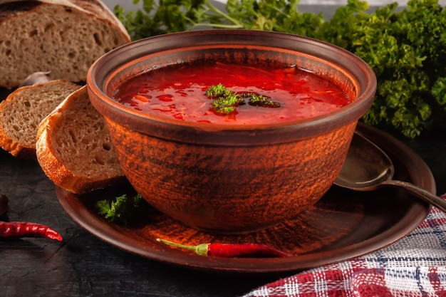 Borsch - beetroot soup in a clay bowl on a stone background,traditional dish of ukrainian cuisine.