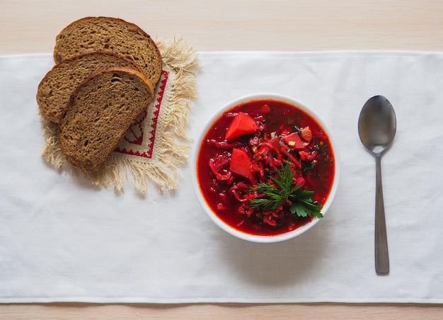 Borsch- 우크라이나 요리의 전통 요리 나무 배경에 흰색 그릇에 사탕 무 우 수프. 평면도.