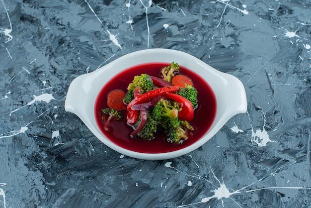 Суп борщ в миске, на синем фоне.