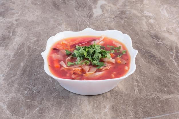Zuppa borsch con contorno di coriandolo su superficie di marmo