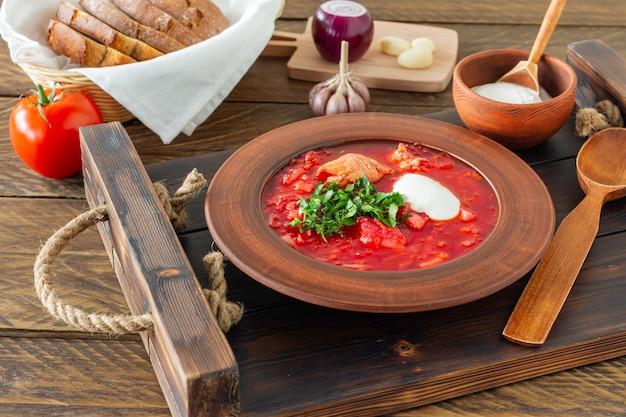 ボルシチ-暗い木製の背景に伝統的なウクライナとロシアのビートルートスープ。木製トレイにライ麦パン、にんにく、塩を添えて。