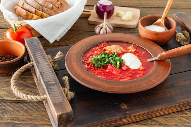 Борщ - традиционный украинский и русский свекольный суп на темном деревянном фоне. подается с ржаным хлебом, чесноком и солью на деревянном подносе.