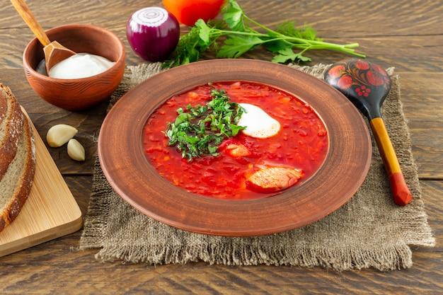 ボルシチ-暗い木製の背景に伝統的なウクライナとロシアのビートルートスープ。ライ麦パン、にんにく、塩を添えて。