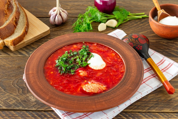 Борщ - традиционный украинский и русский свекольный суп на темном деревянном фоне. подается с ржаным хлебом, чесноком и солью.