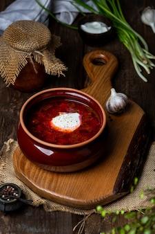 Борщ - традиционный украинский и русский свекольный суп на темном деревянном фоне