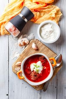肉、ビート、キャベツを使ったボルシチの伝統的なウクライナとロシアのスープ。オレンジ色のボウルに肉のスープ。