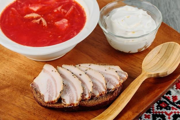 ボルシチウクライナのエスニック料理ウクライナのビートルートスープボルシチのボウルに塩漬けの新鮮なラードサロを添えて...