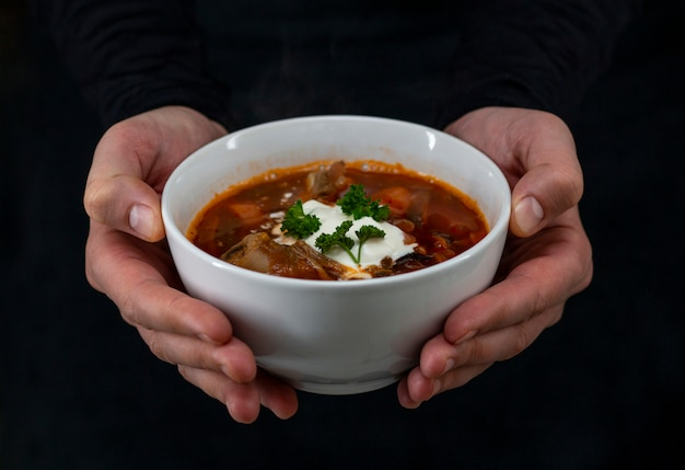 Borsch in a white plate, beetroot soup with sour cream and parsley