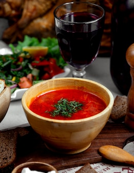 Borsch with herbs and glass of wine
