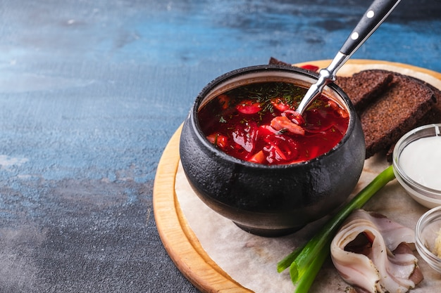 Borsch with sausages and beetroot. traditional  red soup in a  pot.