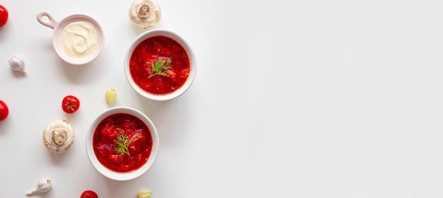 Борщ или традиционный украинский суп из свеклы, помидоров, капусты, моркови и мяса в керамических мисках.