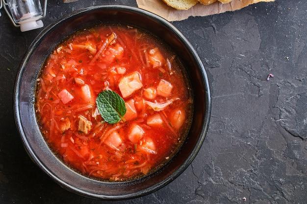 ボルシチの赤いトマトスープの最初のコースのブイヨンの肉と野菜