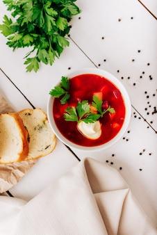Борщ со свежим хлебом на натуральном деревянном фоне. суп из красной свеклы со свежим хлебом