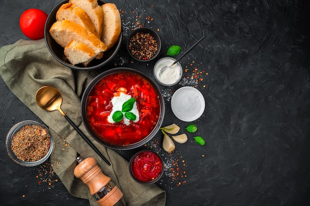 Borscht with sour cream, bread and spices on a black background. top view, horizontal.