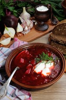 Борщ овощной суп на столе с кусочками хлеба и глютеном сметаны