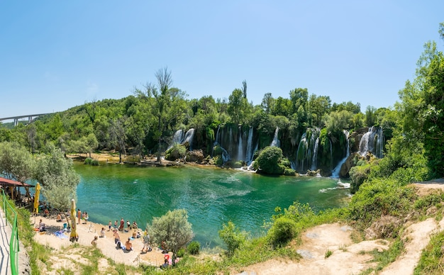 Bosnia and herzegovina tourists rest and swim in the picturesque waterfall
