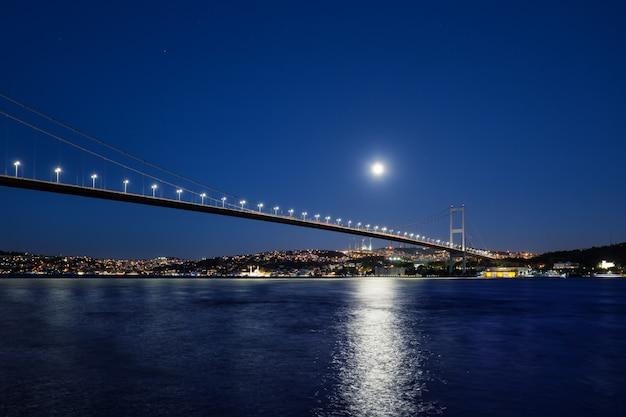 Босфорский мост освещается огнями и лунной ночью