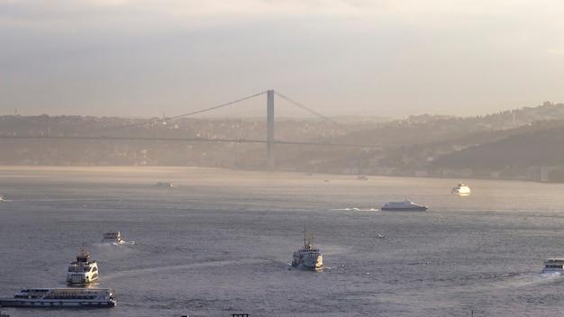 Пролив босфор с плавающими в нем кораблями и мост через воду, туман в стамбуле, турция
