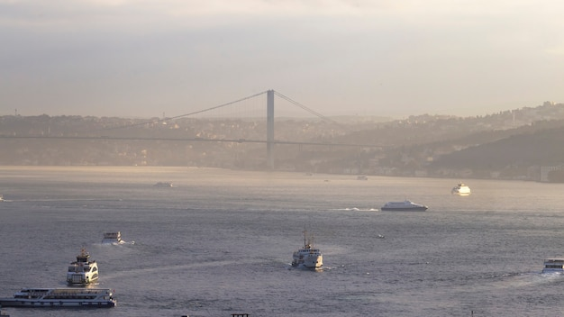 Bosphorus strait with ships floating in it and a bridge over the water, fog in istanbul, turkey