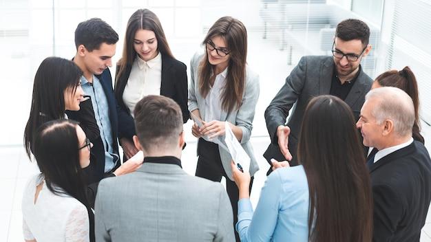 Босс и группа сотрудников обсуждают деловые документы. концепция совместной работы