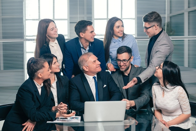 Босс и счастливая бизнес-команда, глядя на экран ноутбука. концепция успешной работы
