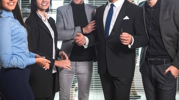 Босс и счастливая бизнес-команда, стоящая в офисном холле. концепция успешной работы