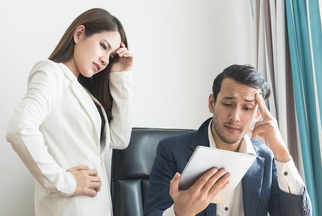 Босс и секретарь подчеркивают, что отчет о бизнес-финансах на планшете