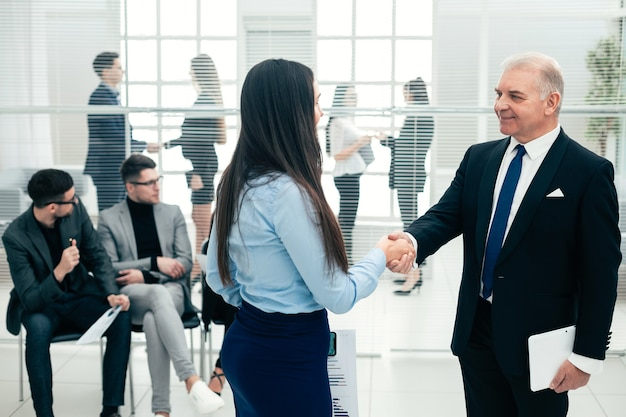 上司とアシスタントがビジネスドキュメントについて話し合います。オフィス就業日