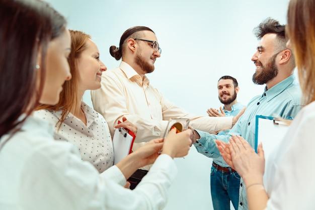 上司が若い成功した従業員を承認し、祝福する