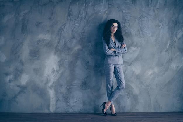 Босс бизнес-леди со скрещенными руками стоит на серой стене