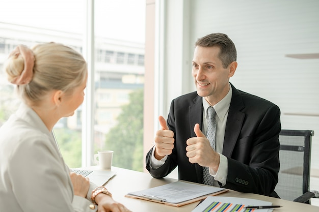 Boss businessman doing thumbs up congratulation to woman employee at desk in office room