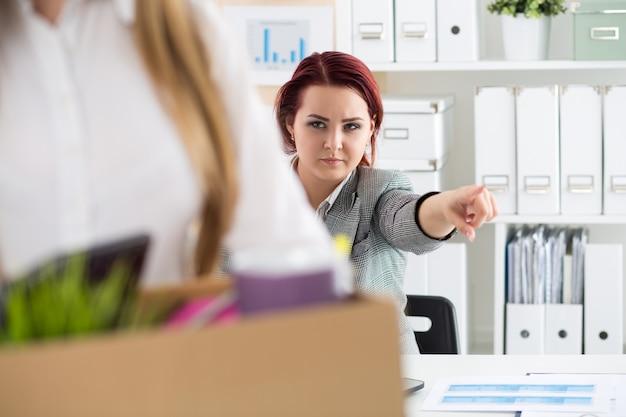 Босс увольняет сотрудника. удрученный уволенный офисный работник несет ящик, полный вещей. получение увольнения концепции.