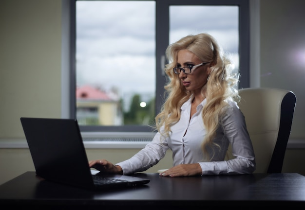 Boss girl sitting at desk in office and working with laptop