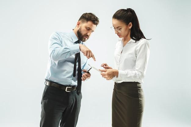 Boss e il suo segretario in piedi in ufficio o in studio.