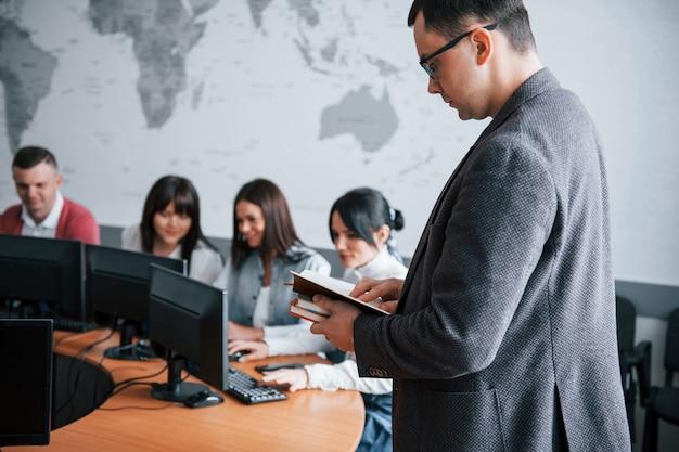 Босс здесь. группа людей на бизнес-конференции в современном классе в дневное время