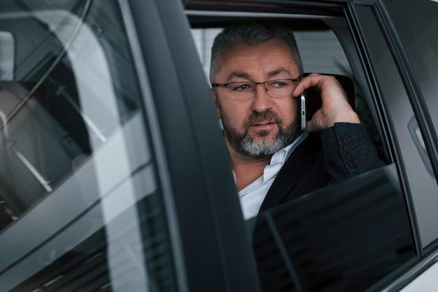 Босс на работе. имея деловой звонок, сидя в кузове современного роскошного автомобиля. старший мужчина в очках и официальной одежде