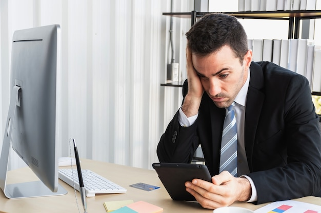Boss is stressing out about the business dealings. a businessman stressing over work on a tablet computer in the office.